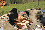A Palestinian woman bakes bread in her neighborhood which experiences power shortages, in Johr El-Deek in Gaza on February 1, 2018. Photo by Ashraf Amra