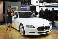 A car girl poses beside a Maserati at the Detroit Auto Show in Detroit, Michigan on January 11, 2009.