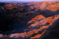 Shadows fall on orange rock in the Valley of the Moon in the Atacama Desert, the driest place on earth. Parts of the desert go for more than a century without recordable precipitation. Flood and wind have left an array of oddly shaped polychrome forms in the desolate, eroded desert landscape.