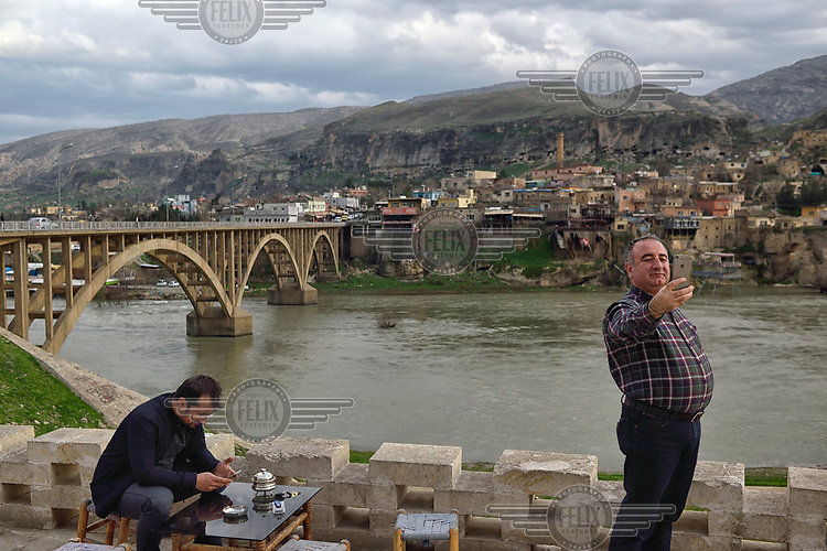 A man takes a selfie with his phone using the Tigris River and the town of Hasankeyf as his background. Much of the town will be submerged beneath 60 metres (200 feet) of water following the completion of the Ilisu hydroelectric dam, 96 kilometres (60 miles) downstream.