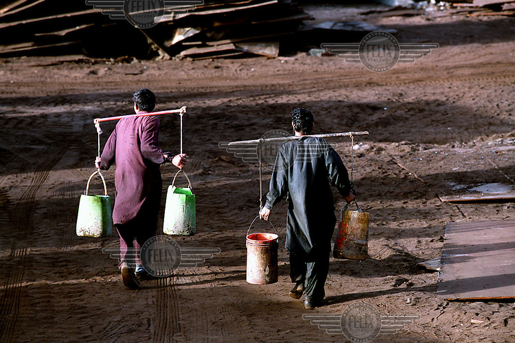 Two workers transport fresh water to their living quarters at the ship-breaking yard in Gaddani.