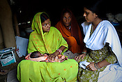 Nutritionist, Neetu Kumari (right) counsels 20 year Asha Devi on breastfeeding her new born child while Asha's mother in law looks on at their hut in village Sanau Sultan in Seohar district in Bihar, India. The NGOs are delivering cost effective interventions to address treatment, care and prevention of diseases, disability and preventable deaths amongst infants, adolescent girls and women of child-bearing age. There is statistical and anecdotal evidence that there have been vast improvements and a total of 40-50% increased immunization for all children under 6 has meant that communities can be serviced and educated long term. Photograph: Sanjit Das/Panos
