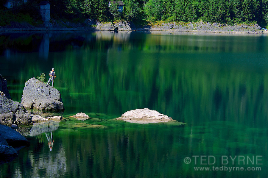 Solitary fisherman on an emerald lake