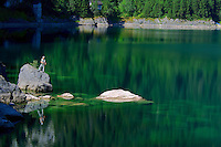 Solitary fisherman on an emerald lake