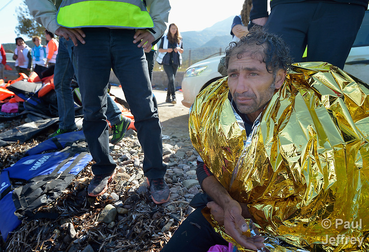 A suspected Turkish migrant smuggler sits on a beach near Molyvos, on the Greek island of Lesbos on October 31, 2015. He was rescued from the water after volunteers on the island punctured a raft in which he was trying to flee back to Turkey after depositing a load of refugees. He was turned over to the Greek police.