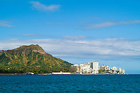 A cluster of small resort hotels and condos front Diamond Head as seen from a sailboat off Waikiki.