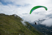A paraglider launches from a ridge line above Eagle River, Alaska.