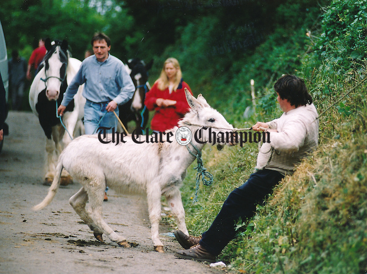 Gerry Hayes from Limerick keeps a tight rein on his donkey at the fair in Spancilhill - July 2, 1999. Photograph by John Kelly
