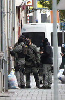 Police surround houses in the Brussels suburb of Molenbeek following Paris Terrorist attack