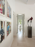 An area of an open-plan room with a sand-blasted stone floor giving a view to a hallway beyond. The minimal, neutral space provides the perfect backdrop to display the owner's collection of artworks, such as a series of pictures by Franziska Maderthaner and a sculpture by artist Bruno Feger.