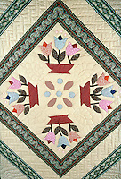 An Amish-made quilt design shows close-up of the four flowers in pots style. Lancaster Pennsylvania United States Amish home.
