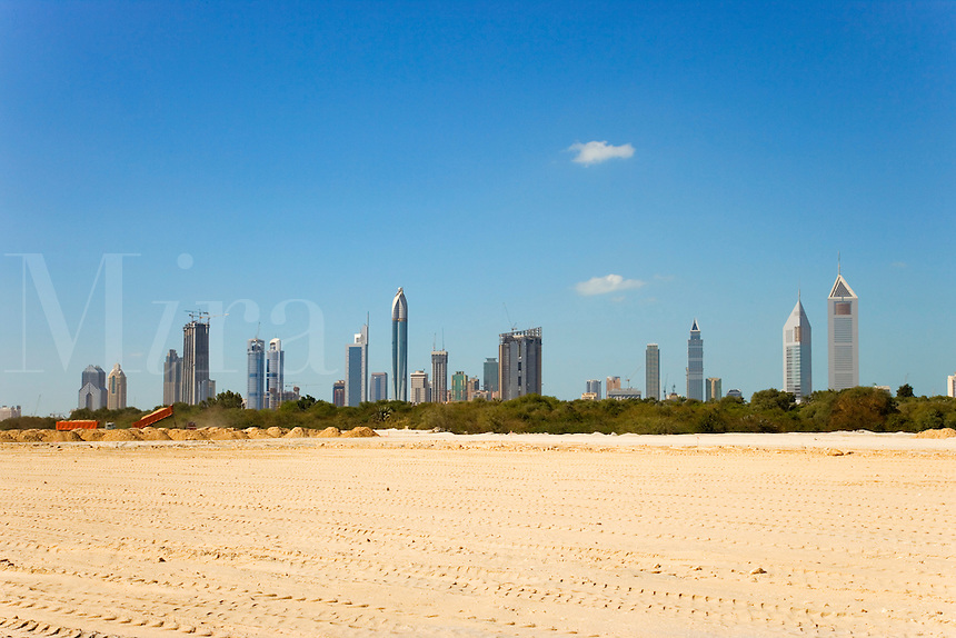 Dubai rises from the desert.  Skyline looking across new building site towards the financial district..