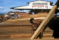Worker carrying cut wood at sawmill in Pucallpa on Ucayali River, Peru