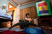 8 year-old Danny Hodes, an Ethiopian boy taken in by Marilyn Berger (not pictured), the widow of Don Hewitt, plays with a mechanical dinosaur in his bedroom in New York, NY, USA, 9 April 2010. Ms Berger met him in Addis Ababa while reporting there and helped him get surgery.