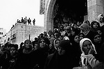Shabab (Palestinian youths) have climbed onto a rooftop while Muslim women look on from the ground as the bodies of four men are paraded around Manger Square in Bethlehem during their funeral. The four men were Islamic Jihad leader Mohammad Shahada, Islamic Jihad militants Issa Marzouq & Imad Al-Kamel, & Al-Aqsa Brigades militant Ahmad Al-Balboul. They were Killed by small arms fire the previous evening from undercover Israeli Special Forces as they waited in a car outside a bakery in Bethlehem. Such killings occur as part of Israel's policy of 'focused foiling' otherwise known as targeted killing: The assassination of individuals considered to be engaged in activity that threatens the security of the Israeli state. 2008.