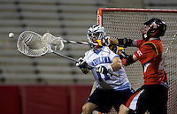 Chris Madalon (11) of North Carolina passes the ball away from Ryan Young (27) of Maryland during the ACC men's lacrosse tournament semifinals in College Park, MD.  Maryland defeated North Carolina, 13-5.