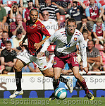 West Ham's Craig Bellamy goes past Roma's Marco Andreolli. .Pic SPORTIMAGE/David Klein