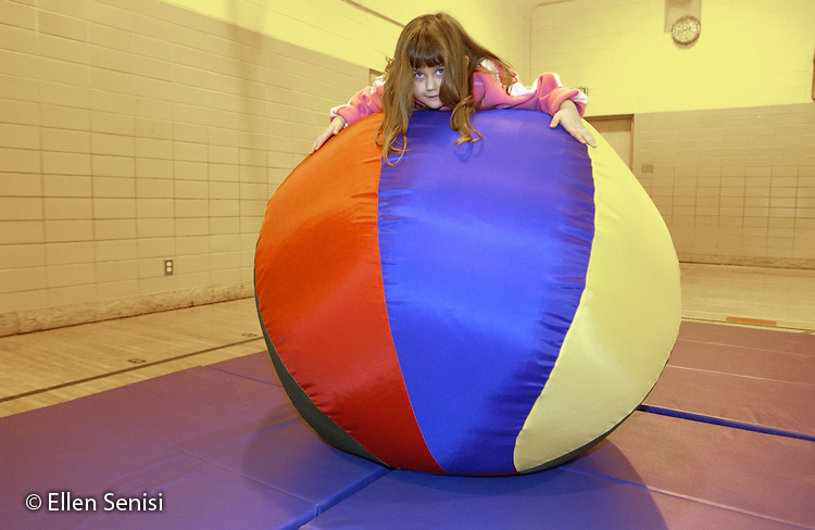 MR / Schenectady, NY                                  .Yates Arts-in-Education Magnet School (urban school).Pre-Kindergarten class; NYS Universal Pre-K Program.Girl (4) balances self on big ball on mat in gym class after being placed there by teacher..Ten2.©Ellen B. Senisi