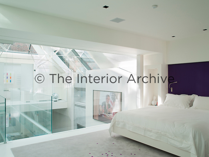The glass wall in the bedroom overlooks the living space below and allows light to flow freely through the upstairs space. The bathroom and stairs are accessed via a glass bridge