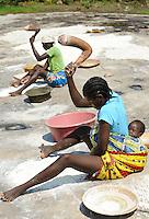 ANGOLA Kwanza Sul, village Catchandja, woman with baby  pound cassava to flour which is used to prepare the mash Funje the staple food in the villages / ANGOLA, laendliches Entwicklungsprojekt ACM-KS, Dorf Catchandja, Frauen stampfen Maniok zu Mehl, das Grundlage fuer Zubereitung des Brei Funje ist