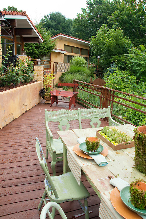 Home deck on two levels, with beautiful rustic wooden table set for eating outside with vases hurricane lamps of hydranges, custom made touches, planters of flowers and containers of vegetables, rose garden, outdoor room and cottage garden feel