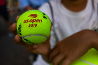 NEW YORK, USA - August 22 : A fan hols a US Open ball on training courts  on August 22, 2019 in New York, USA.<br /> People attend US Open the fan week with Featured practice matches with Roger Federer and Novak Djokovic <br /> (Photo by Luis Boza/VIEWpress)