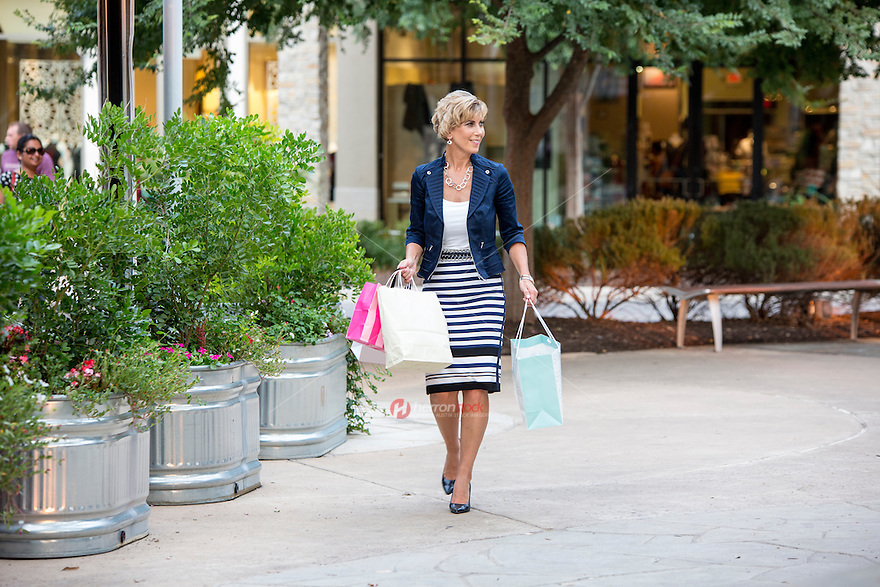 Attractive female shopper with bags in hand accomplishes a busy day of shopping at an Austin outdoor shopping center mall