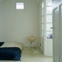 This simple bedroom is sparsely furnished with a Futon covered in a rough blanket accessorised with a small floor lamp