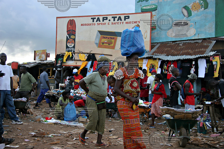 A woman carries a large shopping bag on her head as she walks through a busy street market...