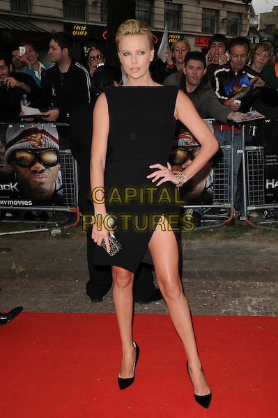"""CHARLIZE THERON.Attending the UK Gala Premiere of """"Hancock"""" at Vue West End, Leicester Square, London, England, UK, June 18th 2008..full length black dress hand on hip shoes thigh slit split gold bracelets .CAP/CAS.©Bob Cass/Capital Pictures"""