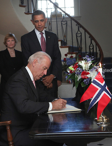 As United States President Barack Obama watches Vice President Joseph Biden Jr. signs the book of condolence at the residence of the Norwegian ambassador.  In the background, Norwegian Charge d' Affairs, Barit Enge. .Credit: Dennis Brack / Pool via CNP