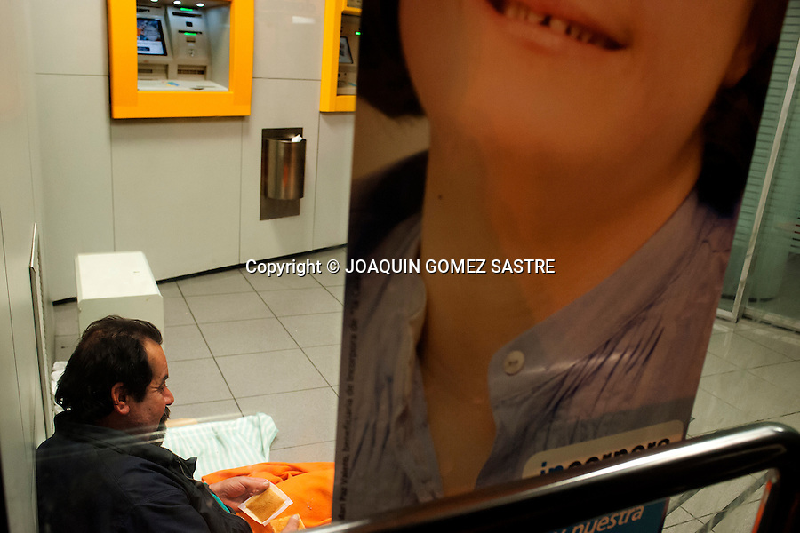 Miguel Angel (was born in Valladolid) 52 years of age, at the ATM of the caixa sleeping in Santander (Spain).photo © JOAQUIN GOMEZ SASTRE