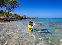 A young boy pauses to lift his snorkeling mask at 'Anaeho'omalu Bay, Big Island.