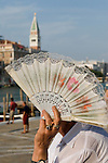 Venice Italy 2009. Woman with fan shading her face. San Marco in distance.