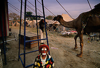 A clown that is a dwarf waits outside the circus tent for the show to begin at a camel mela festival.