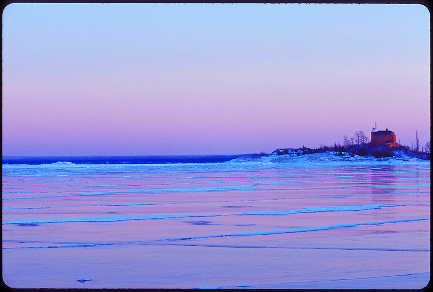 MARQUETTE LIGHTHOUSE WITH FROZEN LAKE SUPERIOR AT DUSK IN MARQUETTE MICHIGAN.