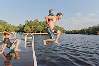Dad Jumping off the Dock with young son on his back.