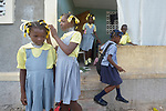 Children get ready for school in the morning in front of one of hundreds of new homes built by Servicio Social de las Iglesis Dominicanas, a member of the ACT Alliance, in the Haitian community of Ganthier in the first year after the devastating passage of Hurricane Matthew in 2016.