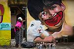 """Senhora observa grafite feito no muro de sua casa na Vila Operária, em Duque de Caxias, durante o evento """"Meeting of favela"""". Rio de Janeiro, 2013."""