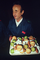 Switzerland. Canton Lucerne. Lunch time in the Sonnenberg tunnel in Lucerne during the largest civil defense exercise ever held in the country. A man carries a tray with plastic plates. A piece of bread, a pork sausage, a melted cheese in aluminium foil and a green apple. From 16 to 21 November 1987, almost 1200 men and women converted a motorway tunnel into perhaps the world's largest bunker structure. The civil protectors had to prove during the exercise «Ameise» ( Ants in english) that in an emergency more than 20,000 inhabitants of the city of Lucerne could survive here in the mountain for two weeks. The Sonnenberg Tunnel is a 1,550m  long motorway tunnel, constructed between 1971 and 1976. At its completion it was also the world's largest civilian nuclear fallout shelter, designed to protect 20,000 civilians in the eventuality of war or disaster. Based on a federal law from 1963, Switzerland aims to provide nuclear fallout shelters for the entire population of the country. The construction of a new tunnel near an urban centre was seen as an opportunity to provide shelter space for a large number of people at the same time. The giant bunker was built between 1970 and 1976 at a cost of 40 million Swiss francs. The shelter consisted of the two motorway tunnels (one per direction of travel), each capable of holding 10,000 people in 64 person subdivisions. A seven story cavern between the tunnels contained shelter infrastructure including a command post, an emergency hospital, a radio studio, a telephone centre, prison cells and ventilation machines. The shelter was designed to withstand the blast from a 1 megaton nuclear explosion 1 kilometer away. The blast doors at the tunnel portals are 1.5 meters thick and weigh 350 tons. The logistical problems of maintaining a population of 20,000 in close confines were not thoroughly explored, and testing the installation was difficult because it required closing the motorway and rerouting the usual traffic. The only l