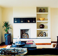 In the family living room, complete with open fireplace, the wenge coffee table introduces an accent of black, the owner's favourite colour
