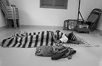 Health center Cambodia . Laying down on a mat, the mother is resting along her baby. A delivery at the center cost 15000 riels (around 4 dollars and 25 cents). Trapeng Andeuk, Takeo province, Cambodia-2009