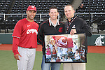 Washington State assistant baseball coach, Spencer Allen (left), and WSU Athletics Director of Major Gifts, Justin Felker (right), pose for a picture with Ol' Crimson flag carrier and Cougar alum, CJ McCoy.  Head coach Donnie Marbut and the entire baseball program presented a signed and framed picture of McCoy waving Ol' Crimson at the NCAA Regional tournament at the University of Arkansas, where the Cougars were playing for a spot in the College World Series.