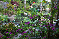 Garden pond framed by New Guinea Impatiens in California cottage garden with sculpture and decorative urn; Sherry Merciari garden