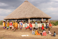Maasai women stand just outside of the table that display their colorful hand-crafted bead work to visitors of their village. The rectangular shaped clothes around their bodies are shukas, and are accompanied by leather or beaded belt. Women in the Maasai community do the majority of the labor, including building and repairing their homes, gathering firewood and water, rearing children, and cooking. This lifestyle begins when, at a young age (around 5th grade), they are sold into marriage and undergo Female Genital Mutilation. The woman is often given as a wife (up to the tenth wife a man has) in exchange for several cows.