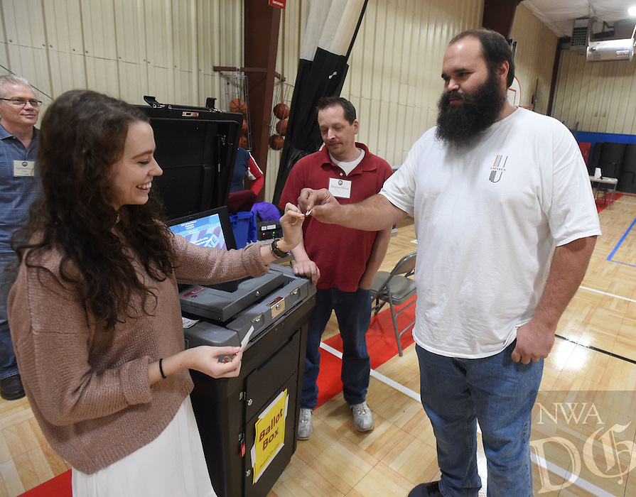 NWA Democrat-Gazette/MICHAEL WOODS &bull; @NWAMICHAELW<br /> Jeff Gray of Fayetteville gets an I voted sticker from volunteer Jenna Blakeman, (left) after casting his ballot November 8, 2016 while election official Joe McKnight (back) and several other election workers help voters get their ballots cast during election day at the Yvonne Richardson Community Center in Fayetteville.