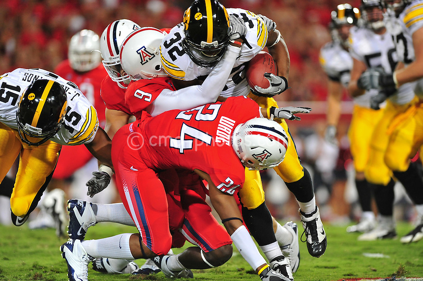 ept 18, 2010; Tucson, AZ, USA; Arizona Wildcats safety Joseph Perkins (9) and cornerback Trevin Wade (24) tackle Iowa Hawkeyes running back Adam Robinson (32) for a loss in the 1st quarter of a game at Arizona Stadium.