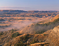 NDTR_124 - USA, North Dakota, Theodore Roosevelt National Park, Morning fog hangs above autumn colored plains and sedimentary hills, view south from Boicourt Overlook, South Unit.