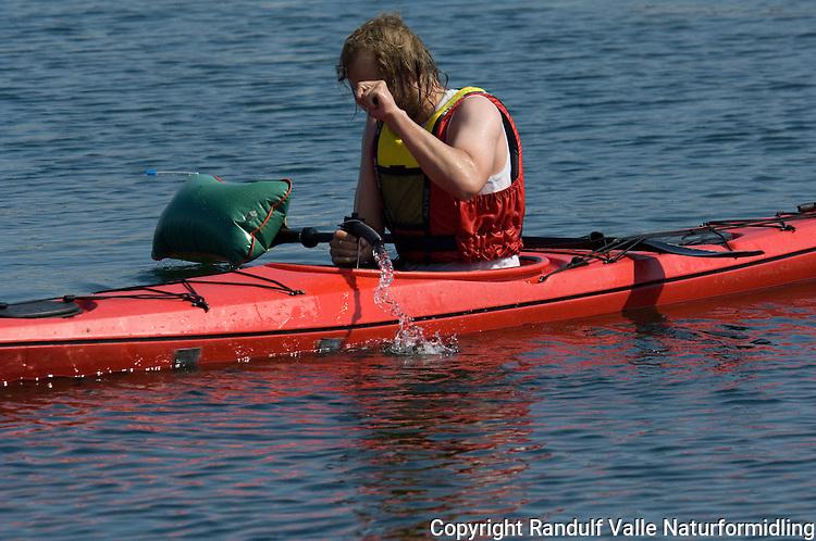 Man pumper vann ut fra kajakk ---- Man pumping water out of kayak