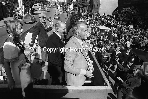Egremont Crabapple Fair, Egremont, Cumbria England 1975. CrabApples are thrown to the assembled crowd. The Crabapple Queen, Bell Ringer Mr P Pattinson and officials Mr W Rickerby and Mr E Whaley tour the village in the back of a lorry.